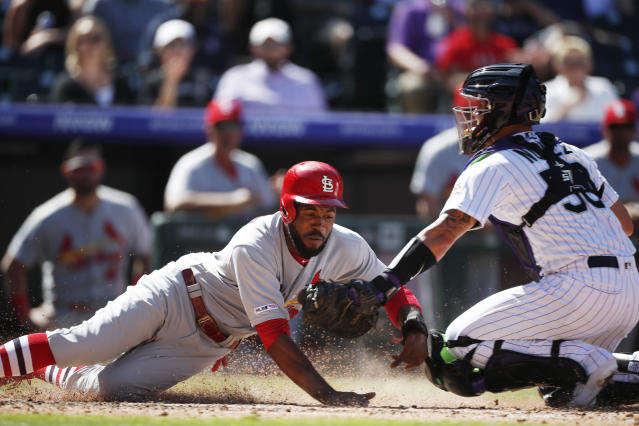 Colorado Rockies catcher Dom Nunez, right, tags out St. Louis Cardinals' Dexter Fowler as he tries to score on a ground ball hit by Paul DeJong in the fourth inning of a baseball game Thursday, Sept. 12, 2019, in Denver. (AP Photo/David Zalubowski)