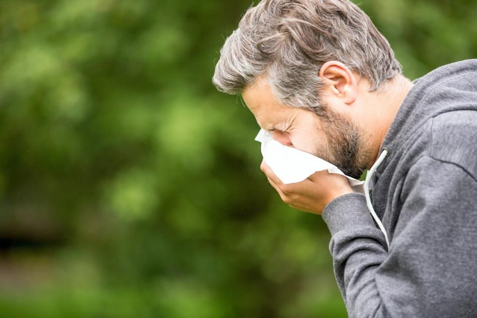 Man with allergy or an infection sneezing
