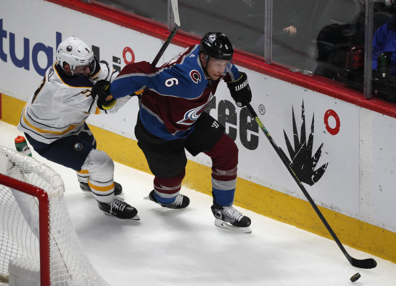 Colorado Avalanche defenseman Erik Johnson, right, picks up a loose puck as Buffalo Sabres center Jack Eichel defends in the first period of an NHL hockey game Wednesday, Feb. 26, 2020, in Denver. (AP Photo/David Zalubowski)