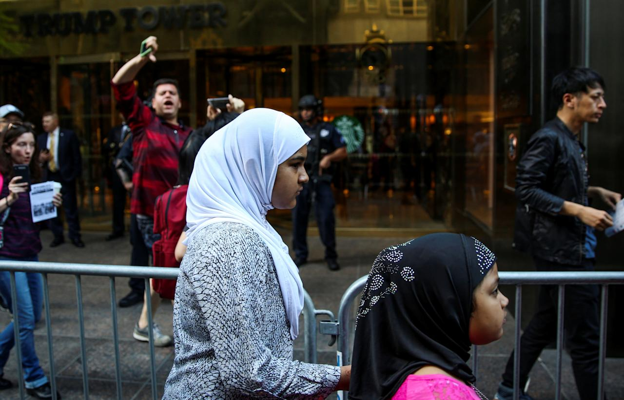 Muslim girls in hijabs walk past a man, as he shouts and gives a 'thumbs down' at activists (not pictured) protesting outside Trump Tower against the U.S. Supreme Court decision to revive parts of a travel ban on people from six Muslim-majority countries in Manhattan, New York, U.S., June 26, 2017.  REUTERS/Amr Alfiky