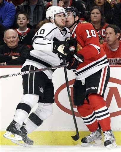 Los Angeles Kings' Mike Richards (10) checks Chicago Blackhawks' Patrick Sharp (10) during the second period of an NHL hockey game in Chicago, Sunday, March 11, 2012. (AP Photo/Nam Y. Huh)