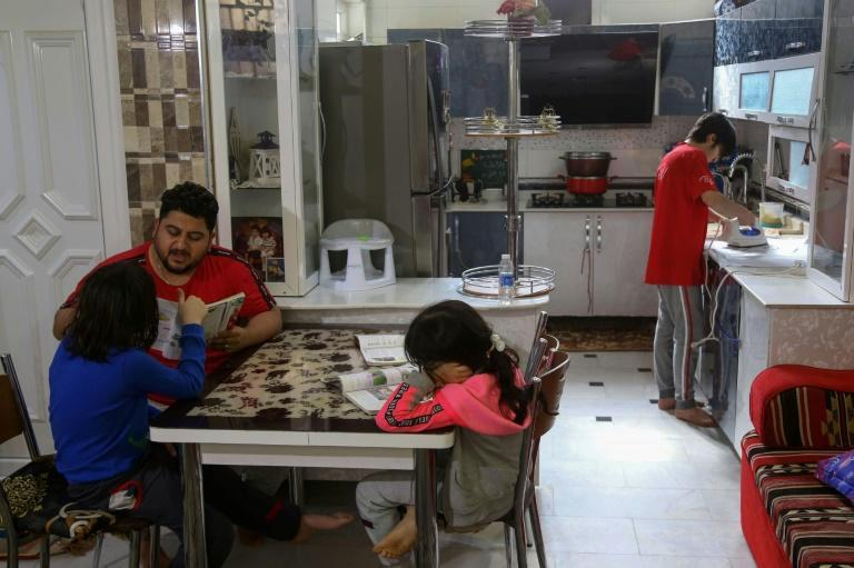 Iraqi engineer Hassanein Mohsen helps his children study at home in Karbala. Mohsen spent months protesting against corruption in Iraq