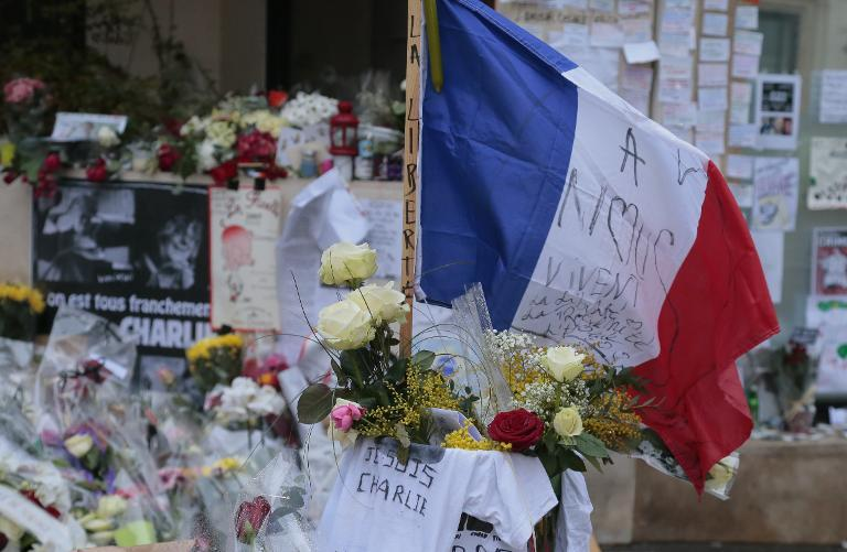 A flag flies among tributes on January 9, 2015 outside the Charlie Hebdo magazine offices in Paris for the victims of the January 7 massacre at the weekly, which left 12 dead