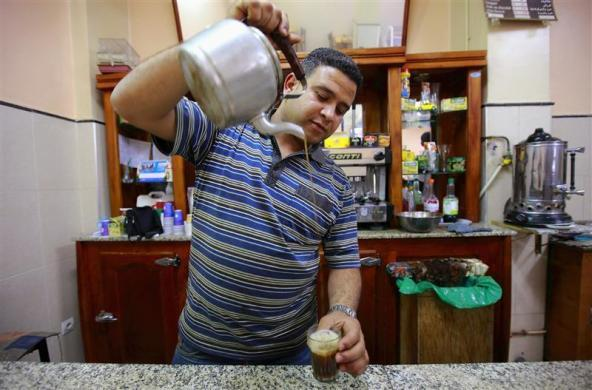 Sofiane Moussaoui, a 26 year-old waiter, poses for a picture as he serves tea for customers in a cafe in Algiers, April 22, 2012. Moussaoui studied for five years at the University 08 May 1945 Guelma where he received a masters degree in corporate finance. He hoped to find a job as an auditor but has been working as a waiter for over a year.