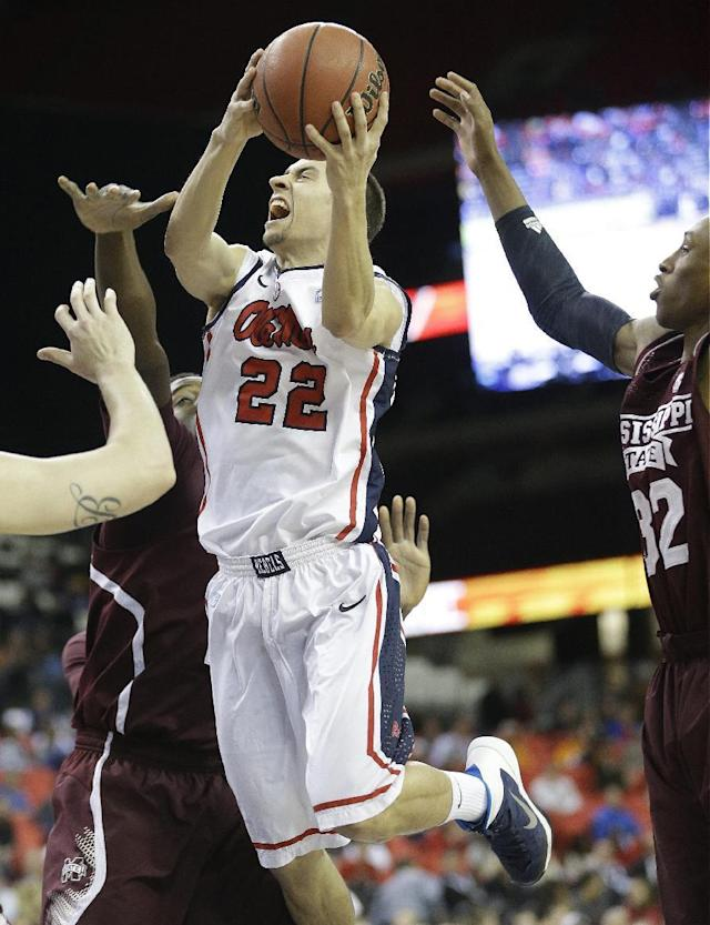 Mississippi guard Marshall Henderson (22) shoots through Mississippi State guard Craig Sword, right, and Mississippi State forward Gavin Ware during the first half of an NCAA college basketball game in the second round of the Southeastern Conference men's tournament, Thursday, March 13, 2014, in Atlanta. (AP Photo/Steve Helber)