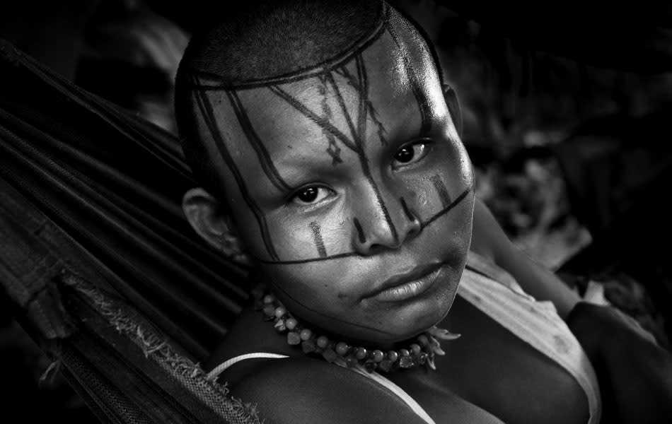 A Nukak woman, having her face decorated with the red dye painted ornaments, lies in a hammock in a refugee settlement close to San Jose del Guaviare on September 04, 2009 in San Jose del Guaviare, Colombia. The Nukak Maku people, nomadic hunter-gatherers from Amazonia, were violently driven out of the jungle by the Colombian guerilla and paramilitary squads. Now, they roughly cut off their original tribal lifestyle and they are stuck between worlds. They learn from the (mainly Christian) aid workers to use clothes, to listen to the radio, to beg for money. Although their digestion suffer, they love to eat sweets, cookies and other western food. They have hunted out all the animals around and now there is nothing left for them. Nukak can not return to the jungle, their world has already passed through an irreversible change. (Photo by Jan Sochor/LatinContent/Getty Images)