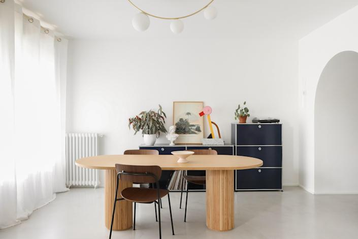 AFTER: In the dining room, &Tradition chairs surround the made-to-measure table by Heju with an Atelier Areti ceiling light above it. A Ettore Sottsass table lamp sits on the USM shelves.