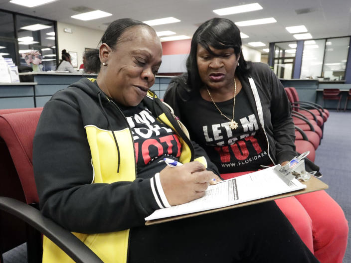 Former felon Yolanda Wilcox, left, fills out a voter registration form as her best friend Gale Buswell looks on at the Supervisor of Elections office Tuesday, Jan. 8, 2019, in Orlando, Fla. Former felons in Florida began registering for elections on Tuesday, when an amendment that restores their voting rights went into effect. (AP Photo/John Raoux)