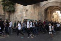 Palestinian protesters march into the Al Aqsa Mosque compound in the Old City of Jerusalem, Friday, Sept. 10, 2021. Amid increased Israeli-Palestinian tension over a recent prison break, Israeli police said an officer was lightly injured by a firearm in an attempt to thwart a suspected stabbing attack in the area. The Police, which arrested the suspect, did not immediately say how the officer was injured. (AP Photo/Maya Alleruzzo)