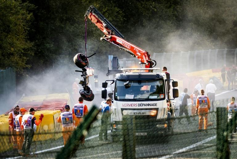 Track marshals look on as a crane lift parts of Correa's car off the Spa track