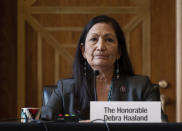 """FILE - In this Tuesday, Feb. 23, 2021, file photo, Rep. Deb Haaland, D-N.M., listens during the Senate Committee on Energy and Natural Resources hearing on her nomination to be Interior secretary, on Capitol Hill in Washington. Some Republican senators labeled Haaland """"radical"""" over her calls to reduce dependence on fossil fuels and address climate change, and said that could hurt rural America and major oil and gas-producing states. The label of Haaland as a """"radical"""" by Republican lawmakers is getting pushback from Native Americans. (Jim Watson/Pool Photo via AP, File)"""