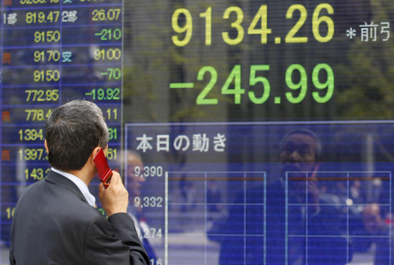 A man speaks on a mobile phone in front of a securities firm's electronic stock board in Tokyo, Monday, May 7, 2012. Asian stock markets were pummeled Monday by weekend election results in Greece and France that heightened uncertainty about Europe's ability to solve its debt crisis. Japan's Nikkei 225 index plunged 2.6 percent to 9,134.26. (AP Photo/Shizuo Kambayashi)