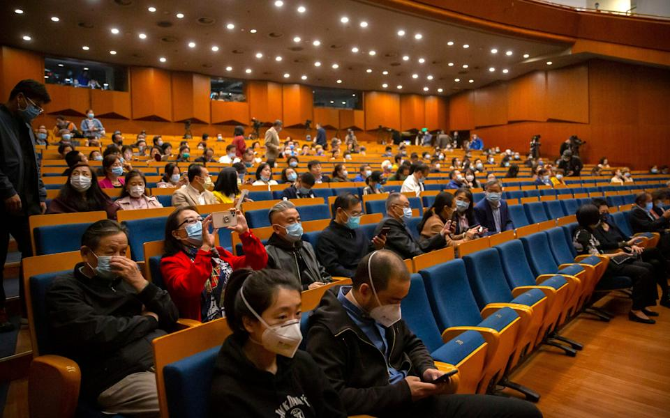 Audience members wearing face masks to protect against the coronavirus take their seats before a concert by the Wuhan Philharmonic Orchestra to open the Beijing Music Festival in Beijing - Mark Schiefelbein/AP Photo