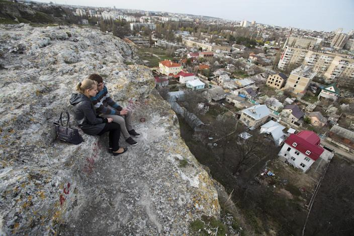 A young couple watches at the town from a hill in Simferopol, Crimea, Tuesday, March 25, 2014. Thousands of Ukrainian troops have began withdrawing from the Crimean Peninsula. (AP Photo/Pavel Golovkin)