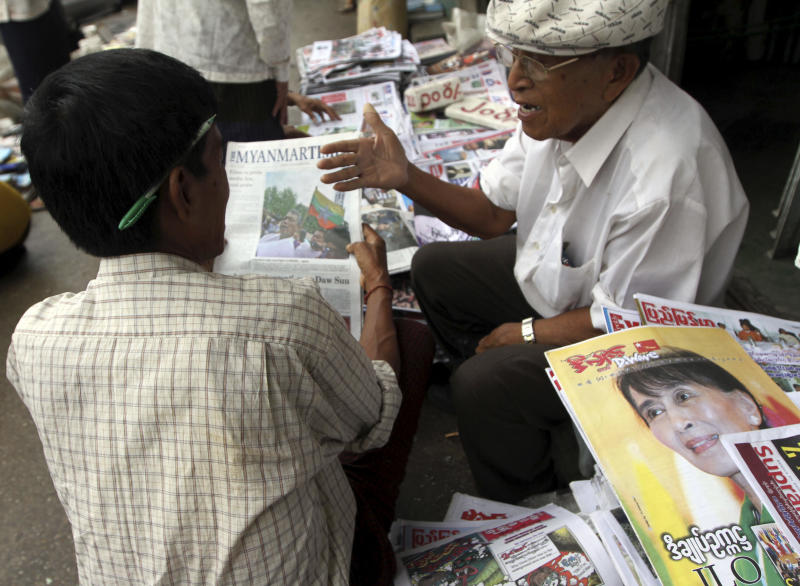 Two men chat each other at a roadside weekly journal shop in Yangon, Myanmar, Monday, Aug. 20, 2012. Myanmar's government said Monday it was abolishing the harsh practice of directly censoring the country's media, the most dramatic move yet toward allowing freedom of expression in the long-repressed nation. Under the new rules, journalists will no longer have to submit their work to state censors before publication as they for almost half a century. (AP Photo/Khin Maung Win)