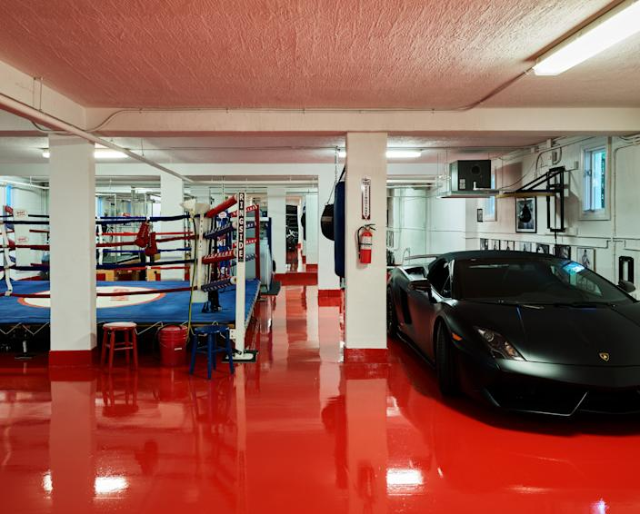 """<div class=""""caption""""> Joyner is an avid boxer and had a full-size boxing ring installed in the basement of the home. The red epoxy floor is an ode to his favorite shade. """"I thought she was going to have a heart attack,"""" Joyner says when describing Wecselman's reaction to the color choice. </div>"""