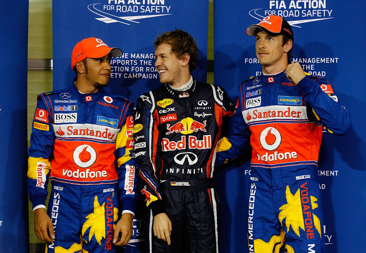 ABU DHABI, UNITED ARAB EMIRATES - NOVEMBER 12:  Pole sitter Sebastian Vettel (C) of Germany and Red Bull Racing celebrates with second placed Lewis Hamilton (L) of Great Britain and McLaren and third placed Jenson Button (R) of Great Britain and McLaren following qualifying for the Abu Dhabi Formula One Grand Prix at the Yas Marina Circuit on November 12, 2011 in Abu Dhabi, United Arab Emirates.  (Photo by Paul Gilham/Getty Images)