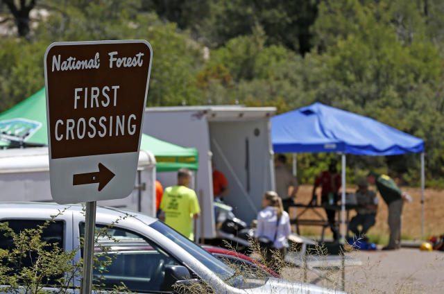 <p>First responders gather near the entrance to the First Crossing recreation area during the search and rescue operation for a victim in a flash flood along the banks of the East Verde River Monday, July 17, 2017, in Payson, Ariz. The bodies of nearly a dozen children and adults have been found after Saturday's flash flooding poured over a popular swimming area in the Tonto National Forest. (AP Photo/Ross D. Franklin) </p>