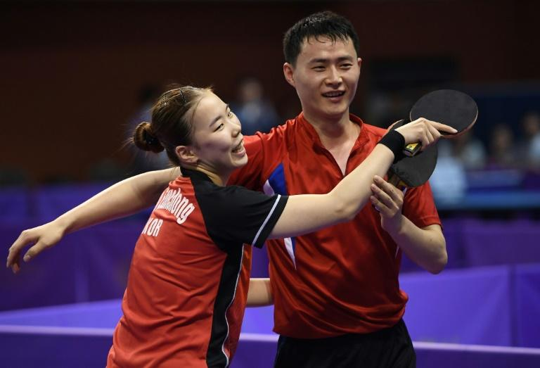 North Korea's Choe Il (R) and his partner South Korea's Yoo Eun-chong (L) celebrate their victory against Spain