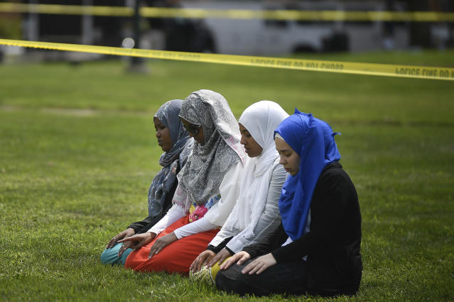 <p>A group of women take part in afternoon prayers led by Dar Al Farooq Islamic Center Executive Director Mohamed Omar outside the police tape surrounding the center, Saturday Aug. 5, 2017 in Bloomington, Minn. (Photo: Aaron Lavinsky/Star Tribune via AP) </p>