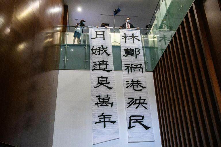 Banners reading 'Carrie Lam, the scourge of Hong Kong and its people' (R) and 'Carrie Lam, leaves a stink for ten thousand years' (L) are displayed by pro-democracy lawmaker Lam Cheuk-ting (top R) outside the main chamber of the Legislative Council