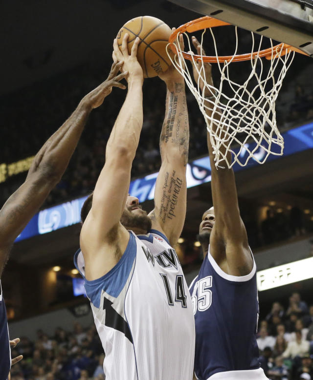 Minnesota Timberwolves' Nikola Pekovic (14) attempts a shot as Oklahoma City Thunder's Kevin Durant, right, and another defender try to block the shot in the first quarter of an NBA basketball game Saturday, Jan. 4, 2014, in Minneapolis. (AP Photo/Jim Mone)