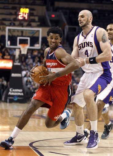 Washington Wizards guard Nick Young, left, drives to the basket past Phoenix Suns center Marcin Gortat, of Poland, in the first quarter of an NBA basketball game Monday, Feb. 20, 2012, in Phoenix.(AP Photo/Paul Connors)