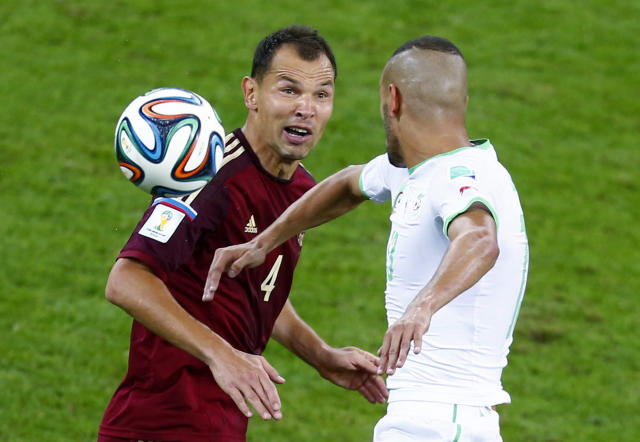 Russia's Sergey Ignashevich (L) and Algeria's Islam Slimani react as they fight for the ball during their 2014 World Cup Group H soccer match at the Baixada arena in Curitiba June 26, 2014. REUTERS/Amr Abdallah Dalsh (BRAZIL - Tags: SOCCER SPORT WORLD CUP)
