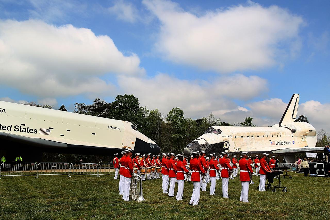 A military band plays as the Space Shuttle Discovery (R), and the Space Shuttle Enterprise (L), sit nose to nose, during an event at the Smithsonian National Air and Space Museum Steven F. Udvar-Hazy Center April 19, 2012 in Chantilly, Virginia. The space shuttle Discovery is the he oldest and most traveled vehicle from NASA's space shuttle program, and will replace the Interprise at the museum.  (Photo by Mark Wilson/Getty Images)