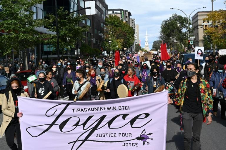 """People hold a """"Justice for Joyce"""" sign during a demonstration in Montreal on October 3 2020, to demand action for the death of Joyce Echaquan, a Canadian indigenous woman subjected to live-streamed racist slurs by hospital staff before her death"""