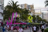 Tourists make their way down Ocean Drive during Spring Break in Miami Beach, Fla. on Monday, March 22, 2021. (Matias J. Ocner/Miami Herald via AP)