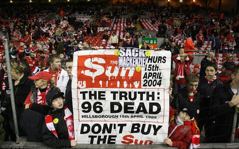 Liverpool fans hold up a sign in reference to The Sun newspaper's controversial front page accusing Liverpool fans of poor behaviour after the Hillsbrough disaster. - Credit: DAVE THOMPSON/AP