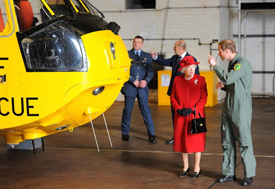 Britain's Queen Elizabeth II (2nd R) is shown a Sea King helicopter by her grandson Prince William (R) during a visit to RAF Valley in Anglesey, Wales on April 1, 2011. Britain's Queen Elizabeth II and Prince Philip, The Duke of Edinburgh today visited RAF Valley in Anglesey and were given a personal tour of an RAF search and rescue helicopter by Prince Willam. AFP PHOTO/ANDREW YATES (Photo credit should read ANDREW YATES/AFP via Getty Images)