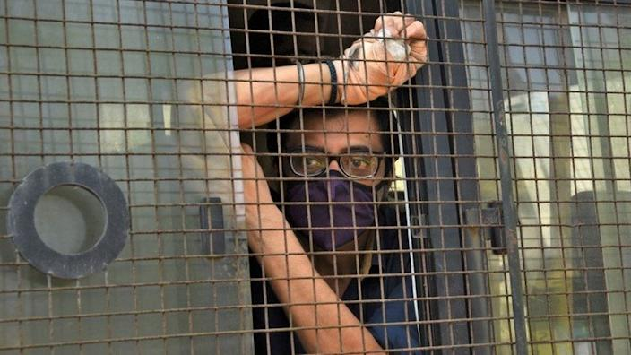"""Arnab Goswami, one of India""""s top TV news anchors, sits inside a police van outside a court after he was arrested, at Alibaug town in the western state of Maharashtra, India, November 4, 2020."""