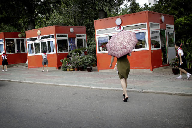 <p>A woman carries a parasol as she walks toward kiosks that sell flowers, snacks and drinks on July 18, 2017, in Pyongyang, North Korea. (Photo: Wong Maye-E/AP) </p>