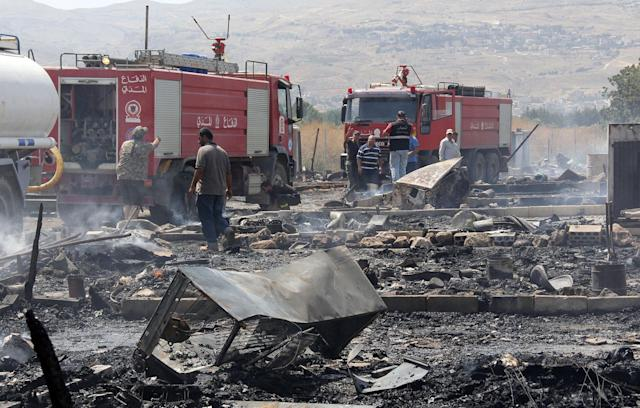 <p>Lebanese firefighters inspect the damage caused by a massive fire in a camp for Syrian refugees near the village of Qab Elias in the Lebanese Bekaa valley on July 2, 2017.<br> A massive fire in a camp for Syrian refugees in central Lebanon killed one person and wounded six others, the Red Cross said, adding that hundreds were evacuated. (Hassan Jarrah/AFP/Getty Images) </p>