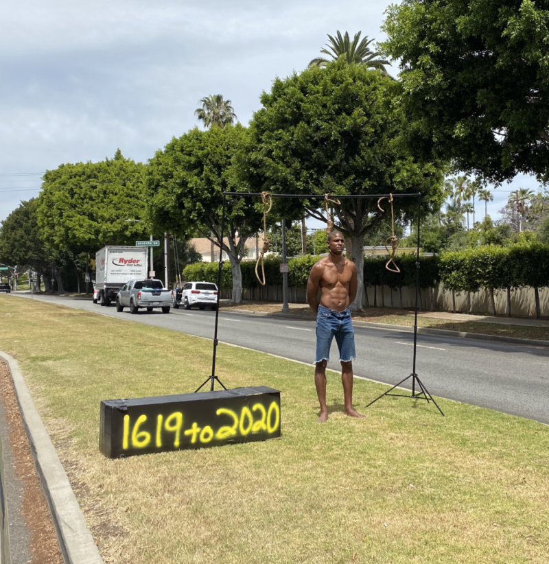 Pictured is a black protester standing in a noose next to a sign that says 1619 to 2020.