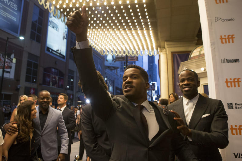 """Director and actor Nate Parker, center, gestures to the crowd as he arrives on the red carpet for the film """"Birth of a Nation"""" during the 2016 Toronto International Film Festival in Toronto on Friday, Sept. 9, 2016. (Chris Young/The Canadian Press via AP)"""