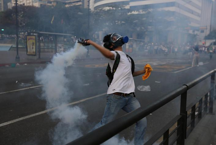 A protester thows a tear gas canister back to riot police during an anti-government protest in Caracas, Venezuela, Saturday, Feb. 22, 2014. After their opposition rally broke up in the late afternoon, in a pattern that has been seen in past demonstrations about 1,000 stragglers erected barricades of trash and other debris and threw rocks and bottles at police and National Guardsmen. The troops responded with volleys of tear gas to prevent the students from reaching a highway and blocking traffic.(AP Photo/Fernando Llano)