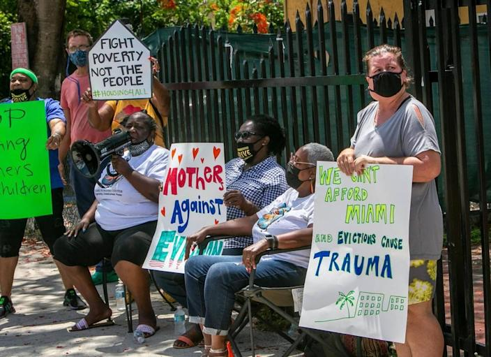 Elena Riech, right, holds a sign in protest in front of the house she rents in Allapattah along with volunteers from the Miami Workers Center who came out to support her on Tuesday, June 8. She could be evicted even though she qualified for governmental assistance because her landlord refused to accept the money.