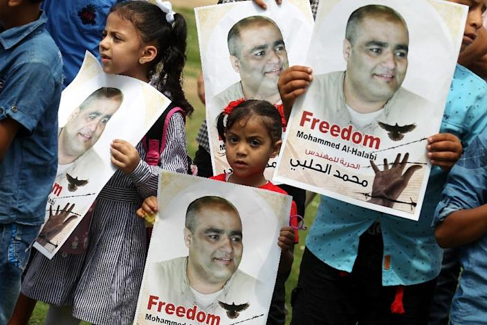 Palestinian children hold posters of Mohammed Halabi, the Gaza director of World Vision, during a protest to support him in the southern Gaza Strip on August 29, 2016 (AFP Photo/SAID KHATIB)