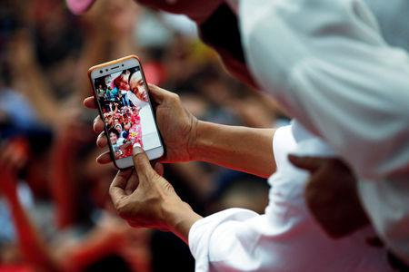Indonesia's president and presidential candidate for the next election Joko Widodo and his wife Iriana Widodo take selfie pictures with their supporters at a carnaval during a campaign rally in Tangerang, Banten province, Indonesia, April 7, 2019. REUTERS/Willy Kurniawan/Files