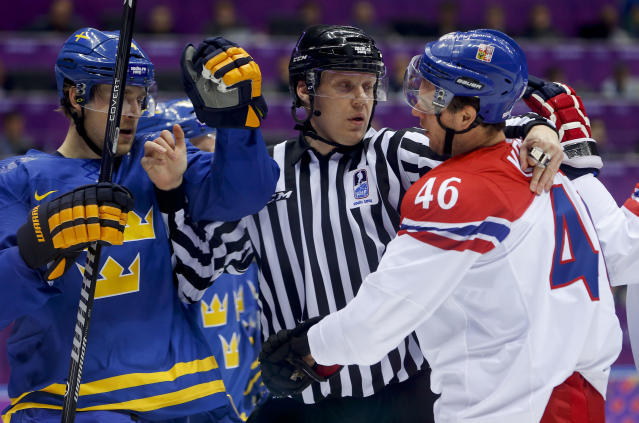 A linesman breaks up a scuffle between Sweden forward Patrik Berglund, left, and Czech Republic forward David Krejci in the first period of a men's ice hockey game at the 2014 Winter Olympics, Wednesday, Feb. 12, 2014, in Sochi, Russia. (AP Photo/Mark Humphrey)