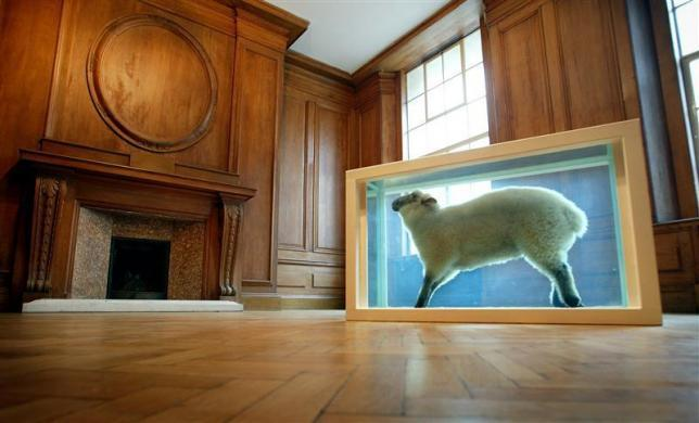 "Damien Hirst's ""Away From the Flock,"" a lamb preserved in formaldehyde in a steel and glass case, is seen on display at the new Saatchi Gallery in London, April 14, 2003."