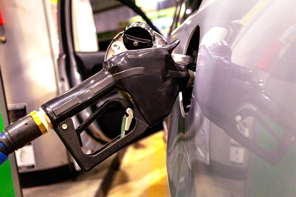 Photograph of a car being refueled at a gas station ( posto de gasolina).