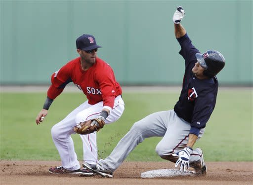 Minnesota Twins' Jamie Carroll beats the tag by Boston Red Sox second baseman Dustin Pedroia on a double in the first inning of a spring training baseball game in Fort Myers, Fla., Sunday, April 1, 2012. (AP Photo/Charles Krupa)