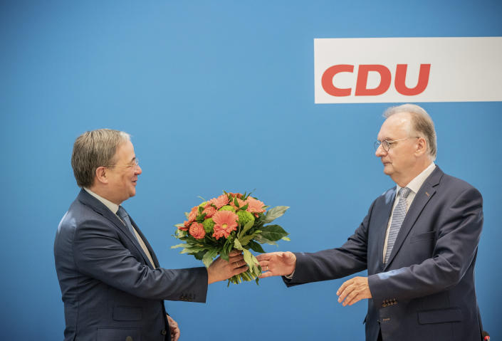 Reiner Haseloff,right, Minister President of Saxony-Anhalt, receives flowers from Armin Laschet, CDU Federal Chairman and Minister President of North Rhine-Westphalia, before the start of the CDU Federal Executive Committee meeting in Berlin, Germany, June 7,2021. The top bodies are discussing the results after the state elections in Saxony-Anhalt. (Michael Kappeler via AP, Pool)