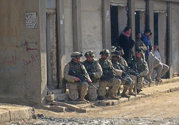 US soldiers raid a neighbourhood in the flashpoint Iraqi town of Fallujah, on 2 January 2004 (AFP via Getty Images)