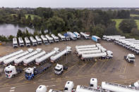 Trucks are parked as part of government's reserve tanker fleet based at a depot in Fenstanton, England, Saturday, Oct. 2, 2021. Military drivers will be deployed to deliver fuel to forecourts from Monday as the crisis at the pumps continues. The British government has extended an emergency visa program for truck drivers as fuel shortages frustrate motorists lining up at empty pumps. (Joe Giddens/PA via AP)