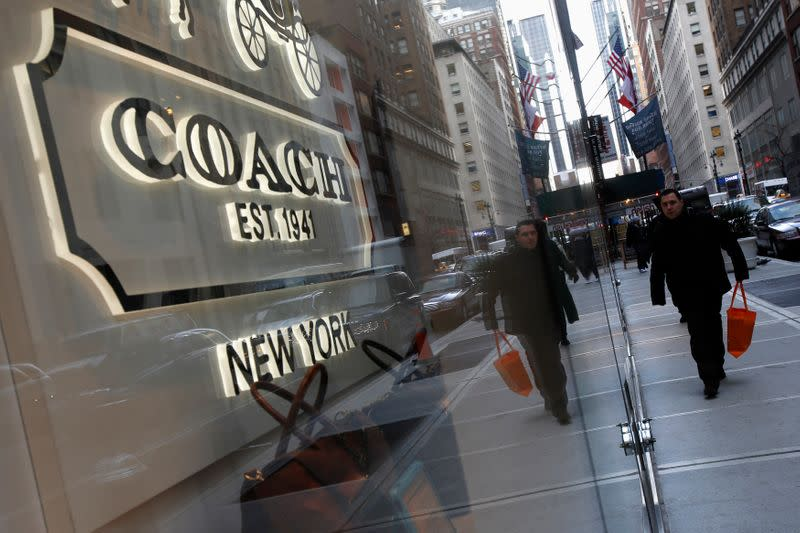People walk past a Coach store on Madison Avenue in New York